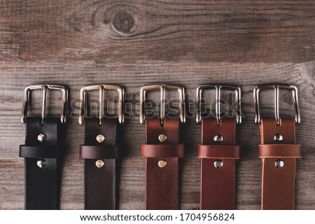 Leather belts in different colors for jeans and chinos on the wooden surface. Royalty-Free Stock Photo #1704956824