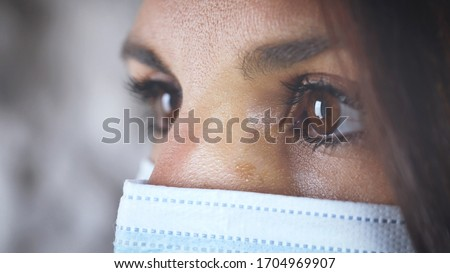Eyes of woman profile close up. looking with surgical mask.  Concept of prevention of Coronavirus virus Covid 19. Medical dispositive protective for hospitals, dentists. close up #1704969907