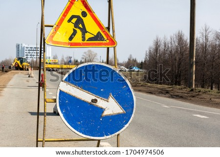 """Repair work. Two road signs """"road works"""" and """"detour obstacles on the right"""" are installed on a portable structure on the road in the city border."""