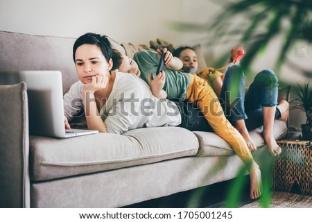 Daytime with family at home. Mother working from home, using laptop. Children playing games on a tablet and watching cartoons.