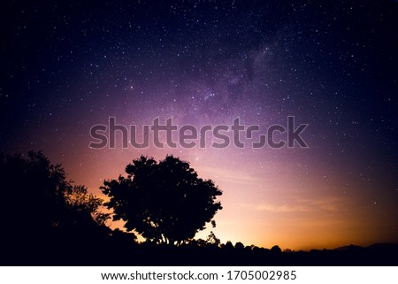 Milky way rising over a landscape silhouette, with a warm glow from nearby city lights visible in the distance #1705002985