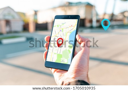 Male hand holding holding smartphone with online-card, which is a red icon of the location. In the background, there is a blurred street and a blue location icon. Concept of online navigation and GPS #1705010935
