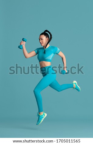 In jump. Beautiful young female athlete practicing in studio, monochrome blue portrait. Sportive fit brunette model with weights. Body building, healthy lifestyle, beauty and action concept. #1705011565