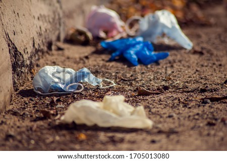Used medical face masks and gloves on the street. Environmental pollution concept  Royalty-Free Stock Photo #1705013080