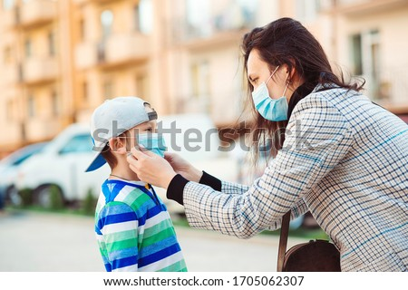 Coronavirus outbreak. Mother puts her son a face protective mask outdoors. Stop the coronavirus spreading. Quarantine. Protective measures. Public crowded place. People prevent infection from virus. Royalty-Free Stock Photo #1705062307