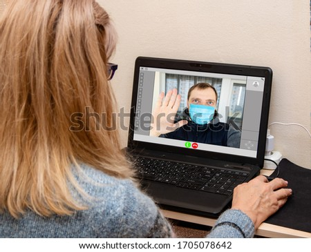 Mature woman having video chat with male in protective medical mask at the table in home. Online call parents. #1705078642