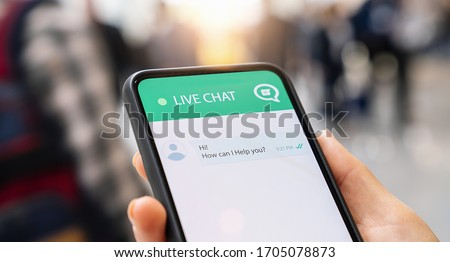 Businesperson use customer service and support live chat with chatbot and automatic messages or human servant outdoor. Assistance and help with mobile phone app. Smartphone helpdesk for feedback cell. Royalty-Free Stock Photo #1705078873