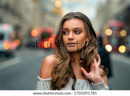 Gorgeous young model portrait in the streets of London with London buses in the back. beautiful bokeh. #1705091785