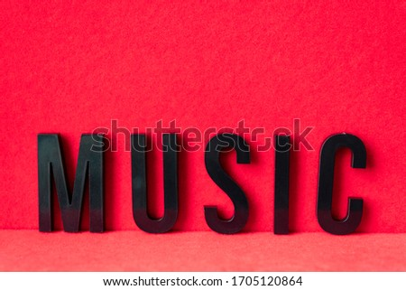 Closeup to a MUSIC black lettering word over a red background. Music lover concept #1705120864