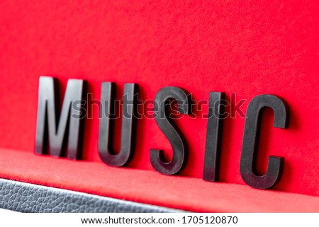 Closeup to a MUSIC black lettering word over a red background. Music lover concept #1705120870