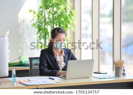 Female employee wearing medical facial mask while working alone because of social distancing policy in the business office reopening during coronavirus or covid-19 outbreak pandemic situation #1705134757