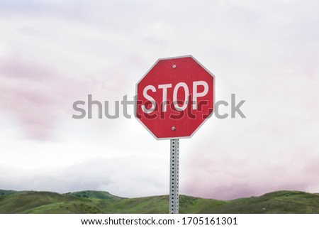 Red stop sign with green  mountain background. Safety and be careful driving. Road trip. Traffic caution, warning, safety drive.