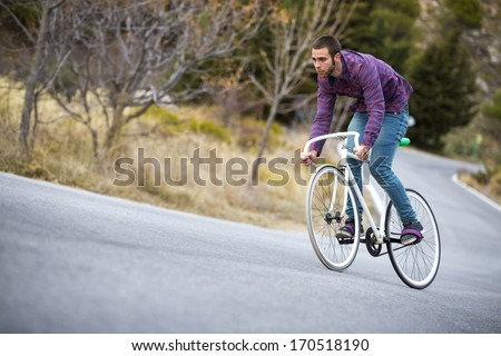 Cyclist man riding fixed gear sport bike in sunny day on a mountain road #170518190