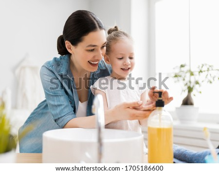 A cute little girl and her mother are washing their hands. Protection against infections and viruses.    #1705186600