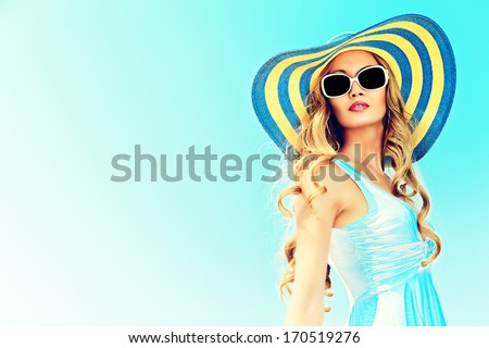 Stunning young woman in elegant hat and sunglasses posing over sky. #170519276