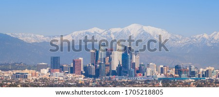 Downtown Los Angeles Skyline with Snow-capped Mountains
