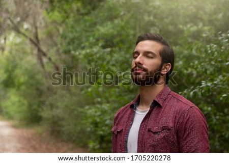 young man with brown hair and beard wearing red button down breathes in a breath of fresh air immersing himself in a nature path to social distance himself in order to stay healthy and alive. Royalty-Free Stock Photo #1705220278