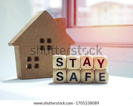 """Stay safe concept. Word """"Stay Safe"""" with wooden house near the window, stay at home, social media campaign for covid-19 or coronavirus pandemic prevention. Royalty-Free Stock Photo #1705238089"""