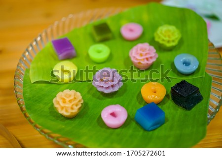 Varieties traditional colorful Thai desserts set; NamDokMai (steaming flour), PiekPoon (black custard), LeumKluen (coconut custard & steaming bean), KanomChan (layer pudding cake) #1705272601