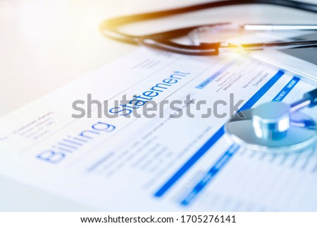Health care billing statement with stethoscope, bottle of medicine for doctor's work in medical center stone background. Royalty-Free Stock Photo #1705276141