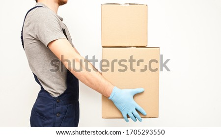 The courier is holding the carton box in his hand wearing  protective latex gloves on the gray background #1705293550