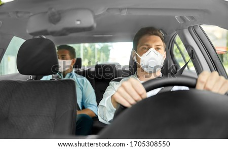 health care, safety and pandemic concept - male taxi driver driving car and passenger wearing face protective mask for protection from virus disease #1705308550