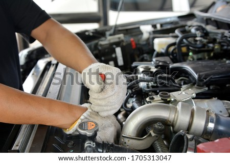 Automotive mechanic working in garage. Repair service. Mechanic working on a diesel engine, close up. Technician hands of car mechanic in doing auto repair service and maintenance worker repairing. #1705313047
