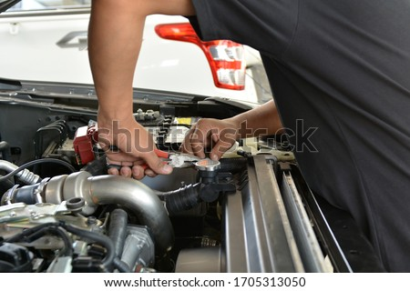 Automotive mechanic working in garage. Repair service. Mechanic working on a diesel engine, close up. Technician hands of car mechanic in doing auto repair service and maintenance worker repairing. #1705313050