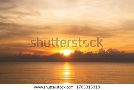 The rising sun over clouds in the sea. The morning light with a beautiful orange sky. #1705315318