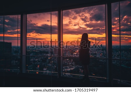 Rear view of Traveler woman looking Tokyo Skyline and view of skyscrapers on the observation deck at sunset in Japan. Vintage tone Royalty-Free Stock Photo #1705319497
