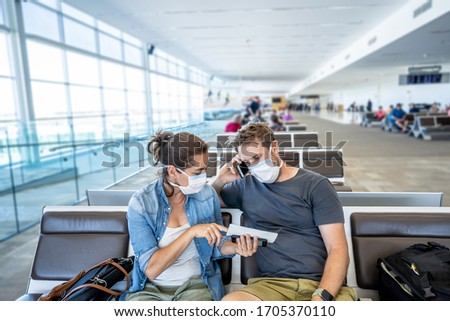 COVID-19 worldwide borders closures. Couple with face mask stuck in airport terminal after being denied entry to other countries. Passengers stranded in airport on his travel back to home country. #1705370110