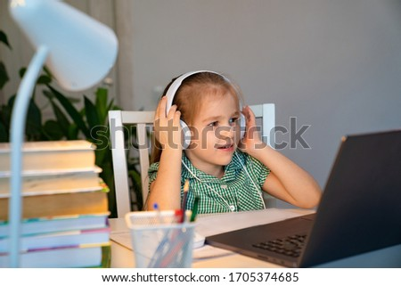 little girl with blond hair in a green dress in headphones listens to music, an audio lesson on the laptop. the social distance. quarantine and epidemic. #1705374685