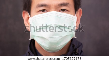 The face of Asian man wearing  N95 mask to prevent PM 2.5 dust and smog germs, toxic fumes, and dust, Prevention of bacterial infection Corona virus or Covid 19 on the black background. #1705379176