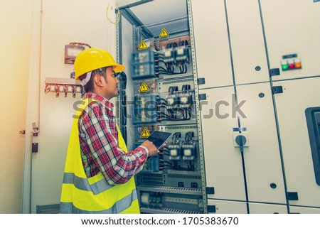 Control Room Engineer. Power Plant Control Panel. Engineer standing in front of the control panel in the control room. Royalty-Free Stock Photo #1705383670