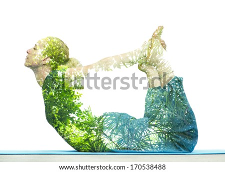 Combining nature with spiritual yoga in a creative portrait of a young woman lying with her body arched holding her toes and her eyes closed in serenity, superimposed with the foliage of trees Royalty-Free Stock Photo #170538488