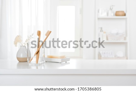 Table with toothbrushes and soap inside a bright defocused bathroom #1705386805