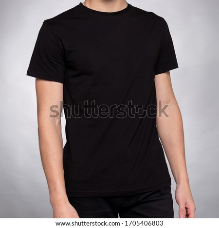 guy in a dark blue plain t-shirt clothes stands with his hands down on a light gray background #1705406803