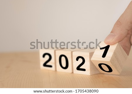 Hand flipping wooden blocks for change year  2020 to 2021 . New year and holiday concept. Royalty-Free Stock Photo #1705438090