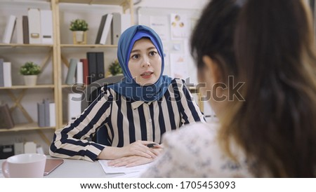 Attentive muslim businesswoman listening to chinese business partner talking during negotiations. multi ethnic people team discuss project. islam financial adviser consulting client meeting in office #1705453093