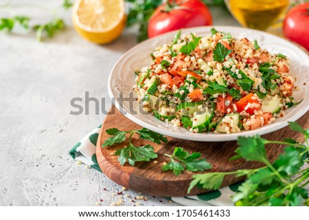Tabbouleh salad - traditional Middle Eastern or Arabic cuisine. Levantine vegetarian salad with bulgur, quinoa, tomato, cucumber, parsley and lemon juice. Tabbouleh with bulgur closeup #1705461433