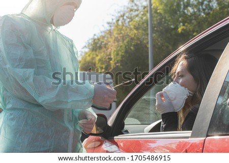 Coronavirus. A medical technician in full protective gear collects a sample from a young woman sitting inside her car. Coronavirus mobile testing unit. Isolated. Quarantine.  #1705486915
