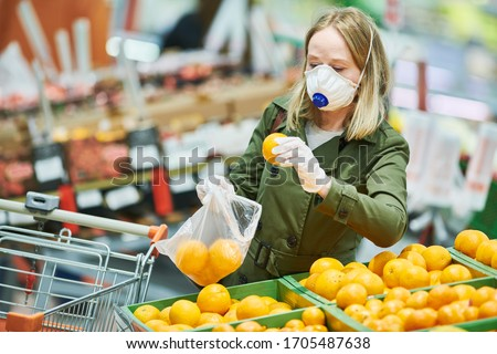 woman in mask and protective gloves buying food in shop at coronavirus epidemic #1705487638