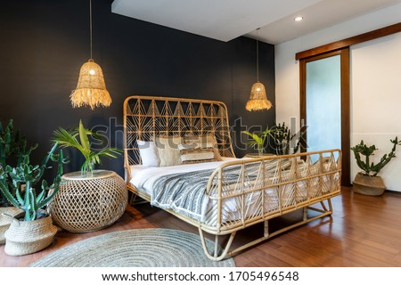 Classic interior bedroom at house with ethnic decor, lamps over bedside tables, wicker headrest at comfortable bamboo bed, carpet or rug and exotical cactus plant in basket near blue copy space wall Royalty-Free Stock Photo #1705496548