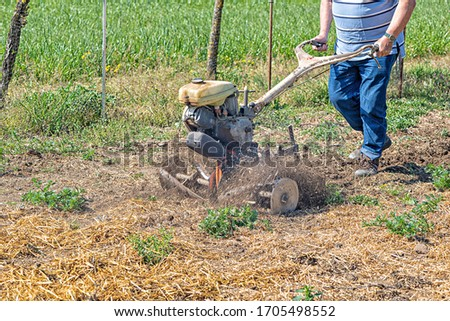 Detail of a monocultor preparing a field to be able to sow it #1705498552