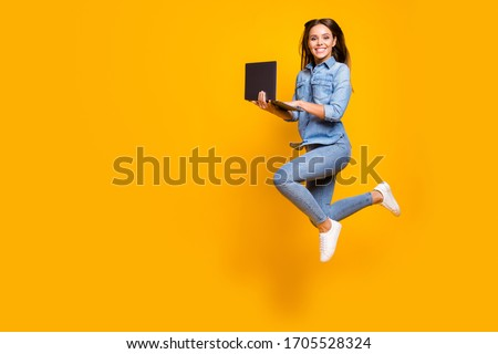 Full length profile photo of funny business lady jump high up hold notebook hands addicted worker always online wear casual denim outfit white sneakers isolated yellow color background #1705528324