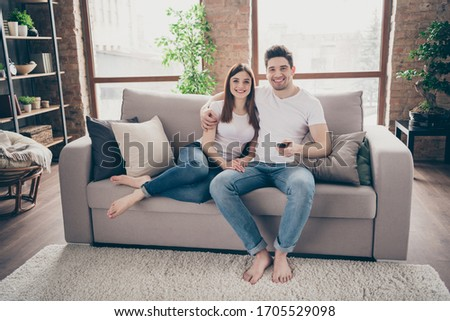 Portrait of her she his he nice attractive lovely cheerful cheery couple sitting on divan having fun watching TV at modern industrial loft style brick interior living-room flat indoors #1705529098