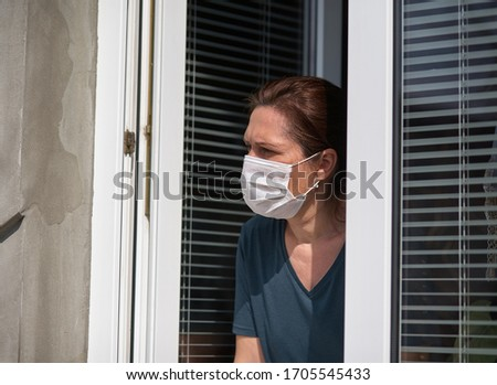 Woman in a medical face mask looks out of the window. Quarantine during the COVID-19 coronavirus epidemic #1705545433