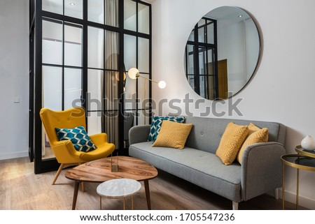 Colorful and cozy living room with a designer armchair and sofa along with a round decorative mirror and glass wall. Royalty-Free Stock Photo #1705547236