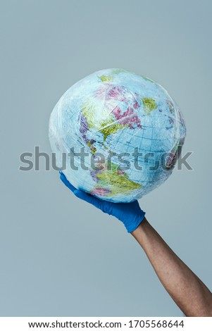doctor man wearing blue surgical gloves holding a world globe wrapped in plastic, depicting the plastic contamination, or the protection against the epidemic infectious diseases or the air pollution #1705568644