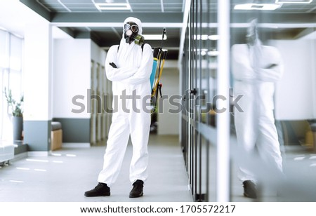 Man in protective hazmat suit in an empty office. Concepts to preventing the spread of coronavirus, pandemic in quarantine city. Covid -19. #1705572217